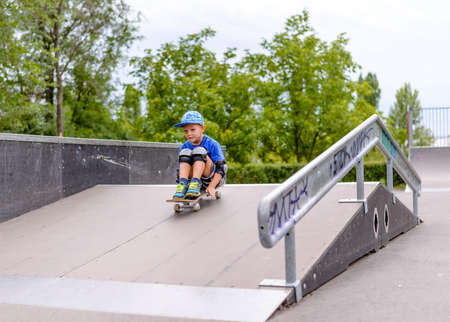 jaunty: Excited little boy trying out his new skateboard at the skate park riding down a ramp balanced on his hands