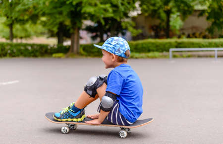 jaunty: Side view of a trendy young boy sitting watching something off the left of the frame on his skateboard at the skate park Stock Photo