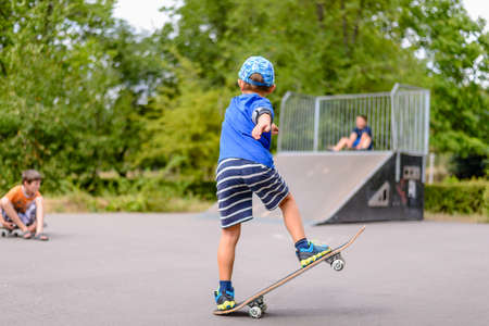 handsome young athletic: Small boy playing with his skateboard at the skate park on a summer day practicing his stance and balance with one end in the air Stock Photo