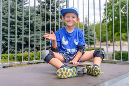 jaunty: Cheeky young boy sitting on his skateboard waving at the camera with a jaunty grin on a ramp at the skate park