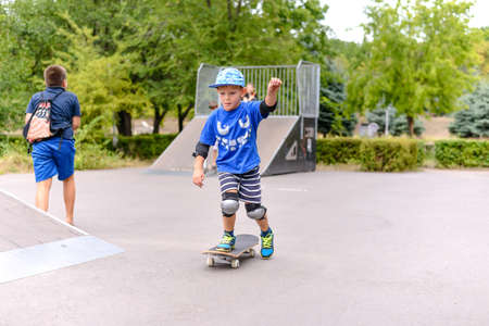 skate park: Cute small boy learning to skateboard pushing himself along on one foot at the skate park with a look of excited concentration