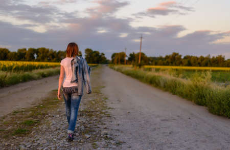 Woman walking away from the camera down a country road in late evening light with her jacket slung over her shoulder, fields of yellow sunflowers on either side