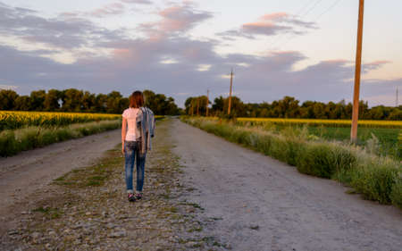 road shoulder: Woman walking away from the camera down a country road in late evening light with her jacket slung over her shoulder, fields of yellow sunflowers on either side