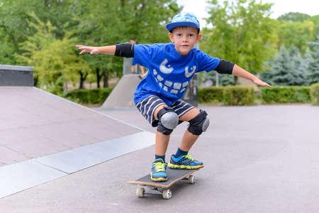 Jongen pronken op zijn skateboard slaan van een stijlvolle pose als hij beoefent zijn vaardigheid bij het skatepark