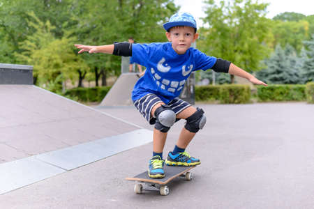 Young boy showing off on his skateboard striking a stylish pose as he practices his skill at the skate park Standard-Bild