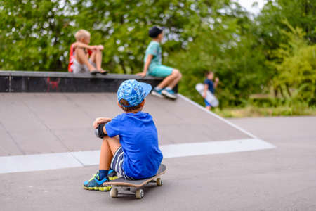 jaunty: Young boy sitting on his skateboard with his back to the camera watching his friends at the skate park Stock Photo