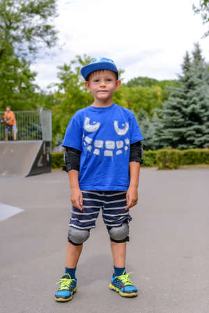 elbow pad: Cute young boy in his trendy blue skateboarding outfit with its protective elbow and knee pads standing at the skate park smiling at the camera Stock Photo