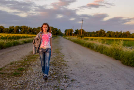 road shoulder: Pretty young teenager standing looking at the camera with her jacket over her shoulder on a country road lined with fields of colorful yellow sunflowers in evening light