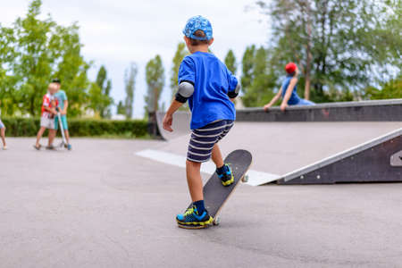 Little boy practicing on his skateboard at the skate park balancing with one end in the air as he watches other youngsters in the distance