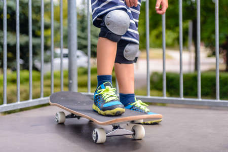 knee: Close up of the legs of a young boy with his skateboard on a ramp dressed in colorful trainers and protective knee caps