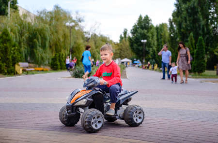hands off: Little boy having fun on a quad bike standing up showing a hands off position with a cheeky grin Stock Photo