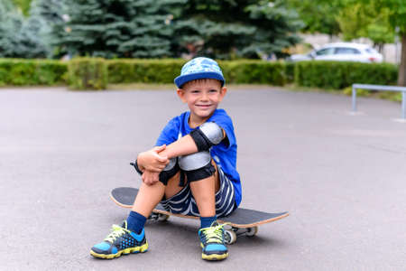 jaunty: Handsome happy young boy sitting on his skateboard at the skate park looking at the camera with a charismatic grin