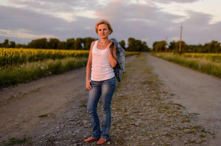 rubia: Atractivo esbelta rubia mujer de mediana edad con su chaqueta colgada del hombro de pie en un camino rural granja entre campos de girasoles al atardecer