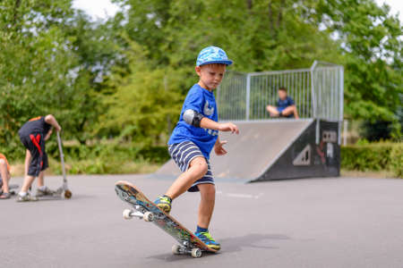jaunty: Small boy playing with his skateboard at the skate park on a summer day practicing his stance and balance with one end in the air Stock Photo