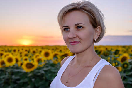 Pretty middle-aged blond woman in the country standing looking to the side of the camera against a colorful sunset over a field of yellow sunflowers