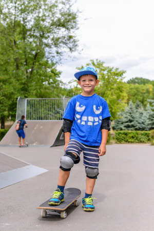 jaunty: Small boy standing on his skateboard at the skate park in a trendy blue outfit with protective gear looking at the camera Stock Photo