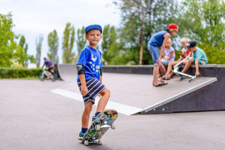 skate park: Young boy at a skate park with friends as they enjoy the freedom of their summer vacation playing on their skateboards Stock Photo