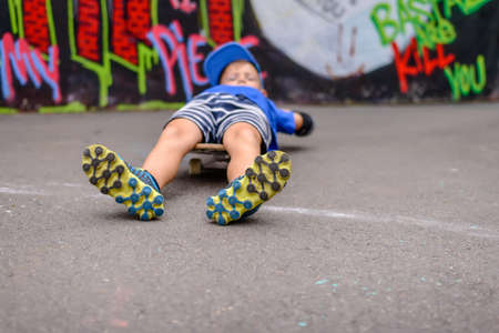 sports recreation: Young boy lying on his skateboard relaxing in front og a colorful graffiti wall with his brightly colored yellow and blue shoes facing the camera Stock Photo