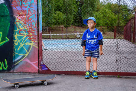 preteen boys: Young boy with his skateboard at a tennis court standing leaning back against the perimeter fence looking at the camera with players visible in the background Stock Photo