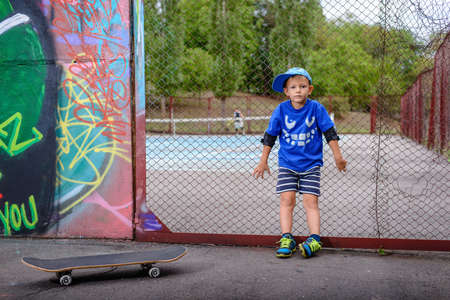 perimeter: Young boy with his skateboard at a tennis court standing leaning back against the perimeter fence looking at the camera with players visible in the background Stock Photo