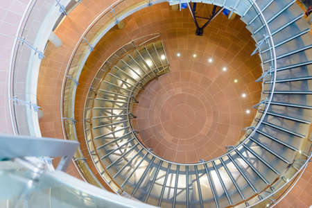 architectural lighting design: Architectural background of a spiral staircase windowing down through the floors of a building viewed from above