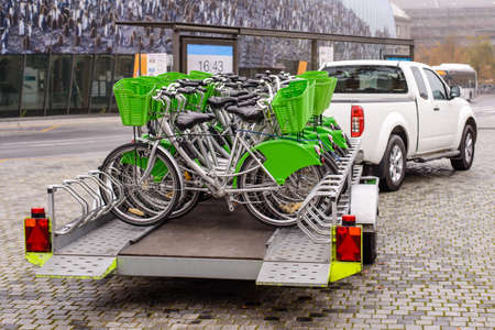 New bicycles with green accessories being transported on a trailer drawn by a pickup van on a cobbled street . view from the back of the bikes 写真素材