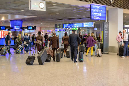emigranti: Frankfurt, Germany- 26 November 2015:Passengers queuing up with their luggage to check in at an airport departures terminal viewed from behind in a travel concept