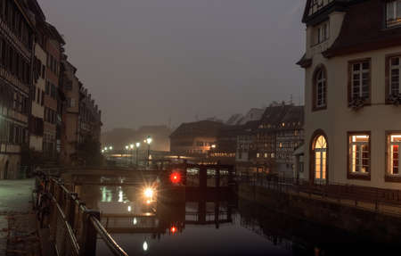 after hours: Night city, houses located on the banks of the river reflected in water streetlights in the fall