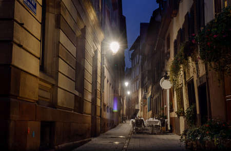 streetlights: Night Street Strasbourg lit streetlights cozy cafe in an alley without customers
