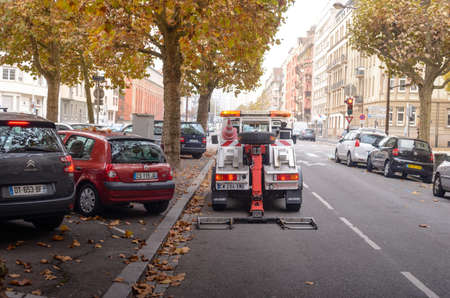 inconvenience: France, Strasbourg - 02 November 2015: City street along the road cars are parked under the tree with yellow leaves on the road is a technical assistance