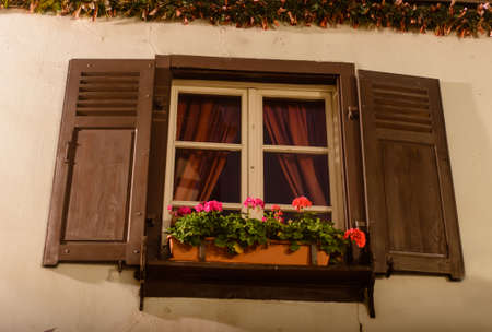 after hours: A window with open shutters beds with red curtains Stock Photo