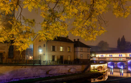 after hours: Night city of Strasbourg , lighting Autumn trees in the fog on the historic waterfront , surrounded by historical buildings