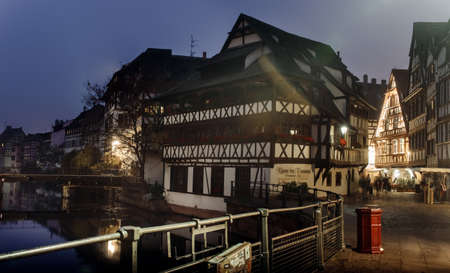 after hours: France, Strsburg-30 October 2015:Night city along the river lit by night lights Lantern in the fog, in the buildings in the windows of the light is Editorial