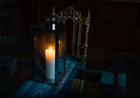 warm house: Close-up lamp with burning candle standing on a glass table in a beautiful interior in a dark room