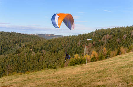 paraglider: Paraglider flying over mountains in summer day Stock Photo