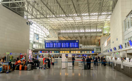 emigranti: Francoforte, Germania-26 ottobre 2015: i passeggeri in fila con i loro bagagli al check-in presso un terminale di partenze aeroporto visti da dietro in un concetto di viaggio Editoriali