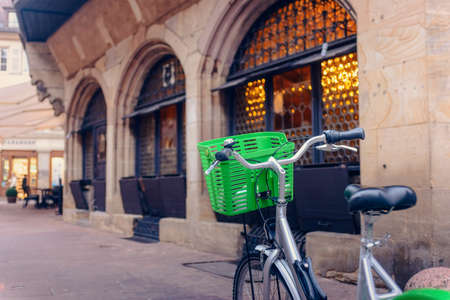 handlebars: Bicycle with a colorful green basket on the handlebars parked outside a commercial urban building in a concept of eco-friendly transport Stock Photo