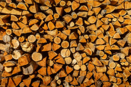 kindling: Wood abstract background. Texture (pattern) of dry firewood in a pile for furnace kindling. Chopped firewood logs. Firewood stack. Close up. Copy space.