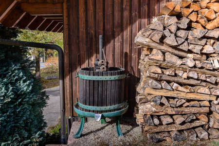 domestic garage: Old fashioned wine press next to pile of cut logs next to wall near garage with tree and gutter