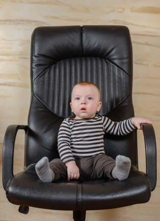 make believe: Fun portrait of a cute chubby little baby boy sitting in a black leather office chair conceptual of his goals and aspirations as a businessman or career