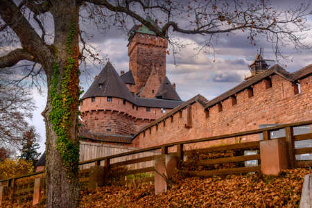 haut: Old medieval castle of Haut-Koenigsbourg or fortress with towers viewed from below looking up an embankment with autumn leaves past a rustic wooden fence