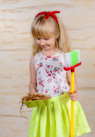 swept: Cute little blond girl with pigtails cleaning house with a toy broom and pan proudly showing off all the wood shavings she has swept up Stock Photo