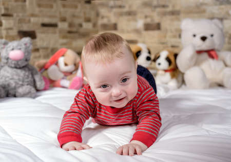 attractive charismatic: Cute baby boy on a bed trying to crawl