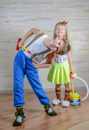 bend over: Cute playful little boy and girl cleaning house together with a toy plastic broom and vacuum cleaner with the boy bending over so that the grinning girl can peer at the camera over his head