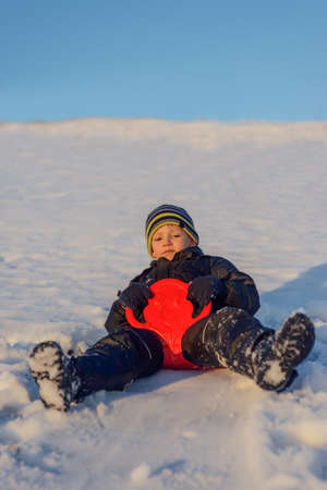 grins: Happy little boy warmly wrapped in winter clothing having fun in fresh white winter snow in evening light as he grins at the camera Stock Photo