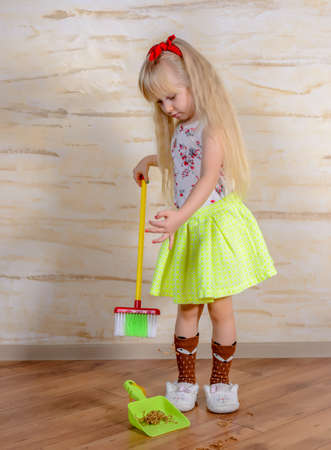 sweeps: Pretty little blond girl cleaning the house with a colorful plastic toy broom and pan bending forward as she carefully sweeps up the dirt, full length close up Stock Photo
