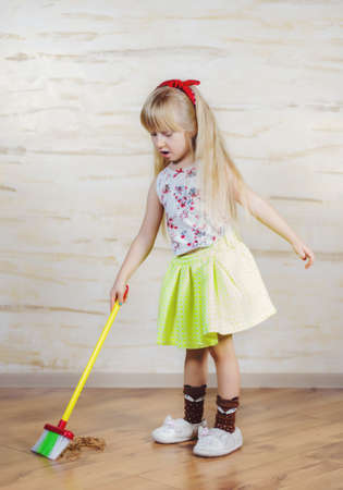 bending forward: Pretty little blond girl cleaning the house with a colorful plastic toy broom and pan bending forward as she carefully sweeps up the dirt, full length close up Stock Photo