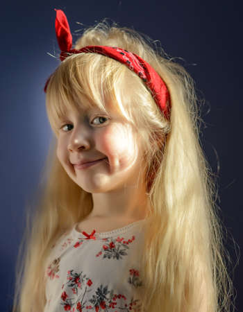 bandana girl: Close up Cute Blond Girl with Red Bandana as Headband Smiling at the Camera Against Gray Background. Stock Photo