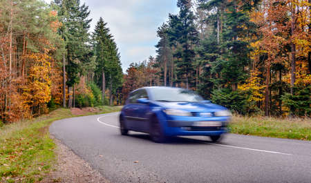 highroad: Speeding car blurred on arred road through colorful autumn trees