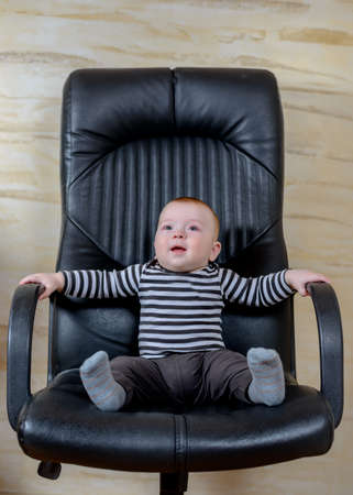 looking away from camera: Cute Baby Boy Sitting on Black Office Chair and Looking Away from Camera with Happy Facial Expression.